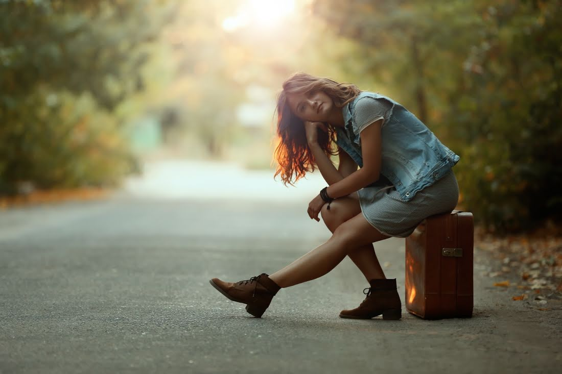 Beautiful young woman sitting on suitcase